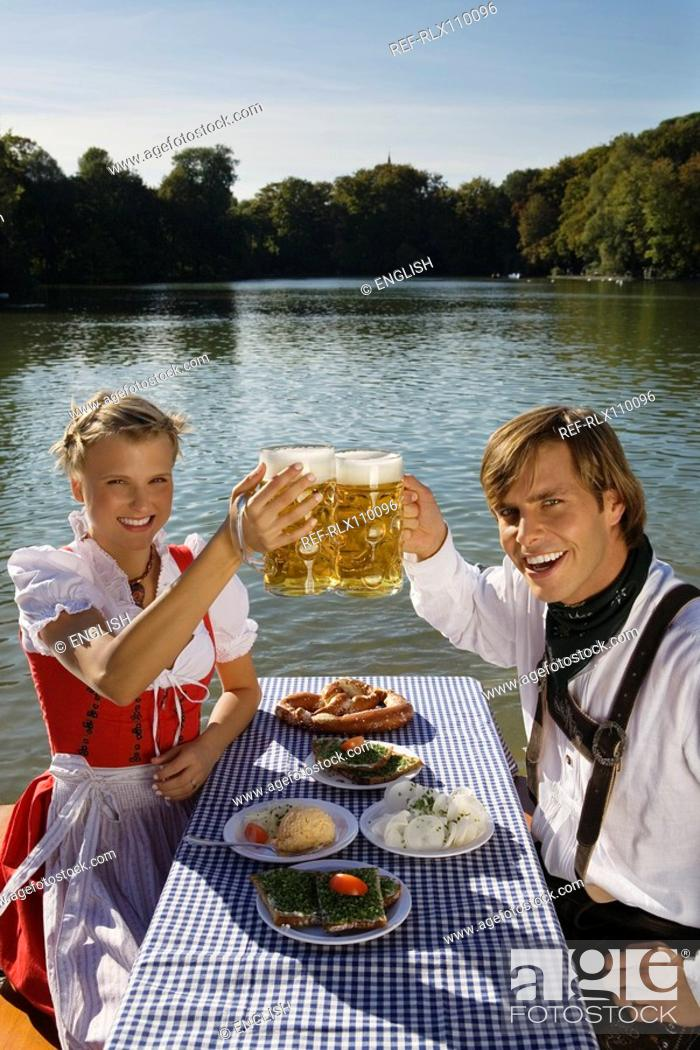 Stock Photo: Young couple in traditional Bavarian outfit, having meal in beer garden, Munich.