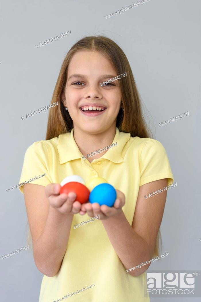 Stock Photo: Portrait of a girl with Easter eggs on a gray background.