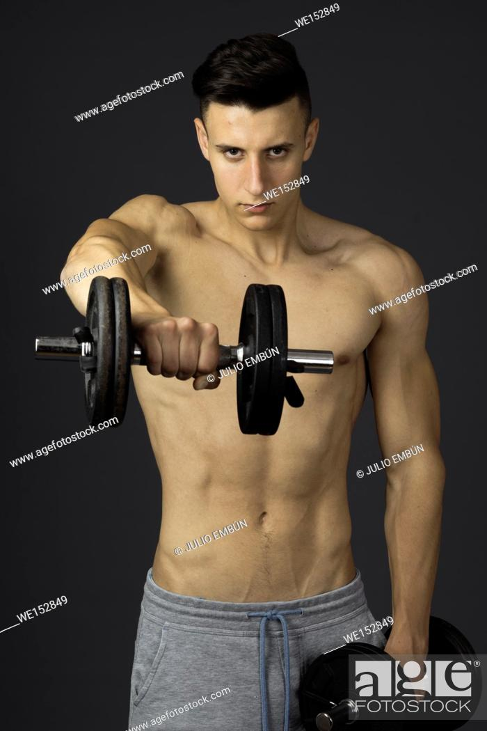 Stock Photo: Young athletic and shirtless boy poses in the studio.