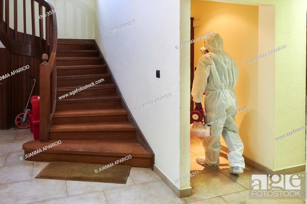 Imagen: Worker in protective suit disinfect interior office.