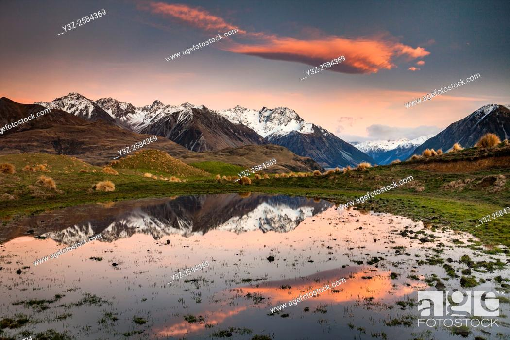 Stock Photo: Dawn lights up peaks in Reishek Mountains, reflection in small pond, Rakaia, Valley, Canterbury, New Zealand.