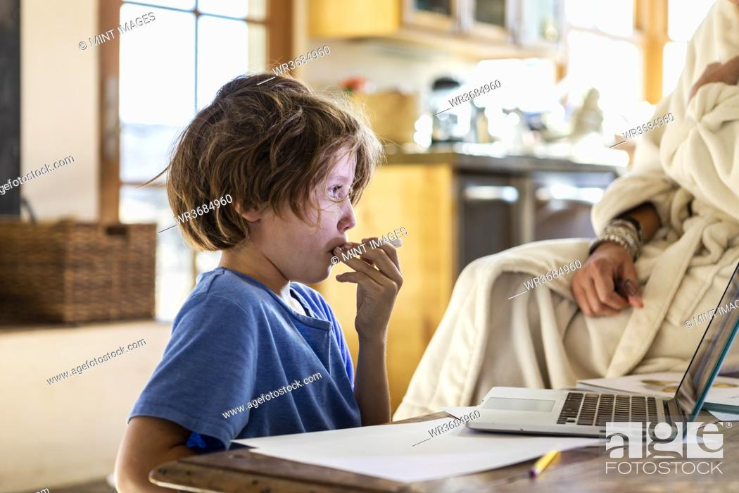Stock Photo: young boy at home having his temperature taken with a thermometer.