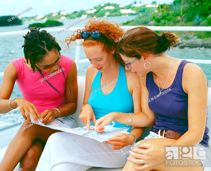 Stock Photo: Close-up of three young women sitting on a bench and looking at a map, Bermuda.