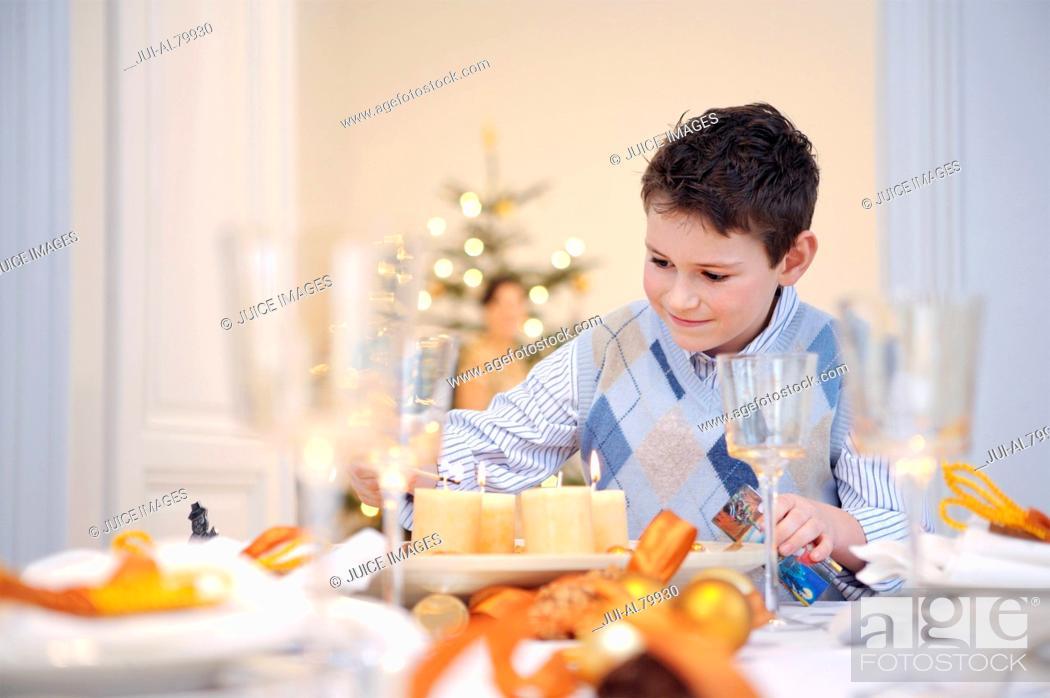 Stock Photo: Boy helping set table at Christmastime.