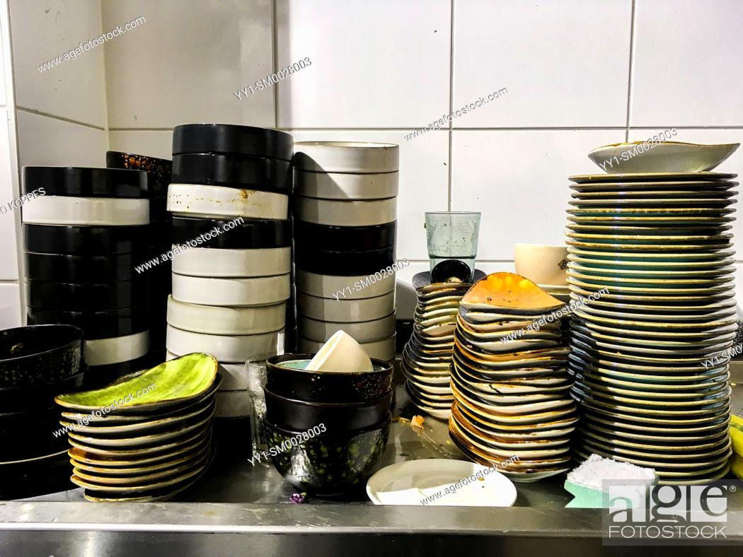 Stock Photo: Tilburg, Netherlands. Multiple stacks of dirty disches to be cleaned and washing inside a restaurant's kitchen.