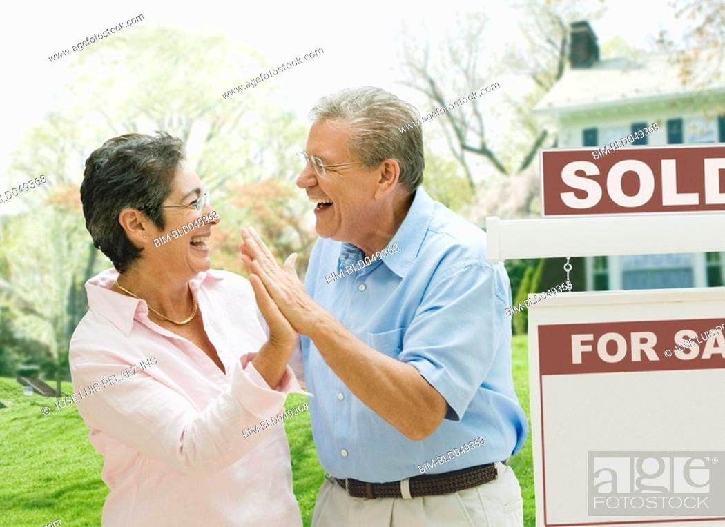 Stock Photo: Senior couple high-fiving in front of new house.