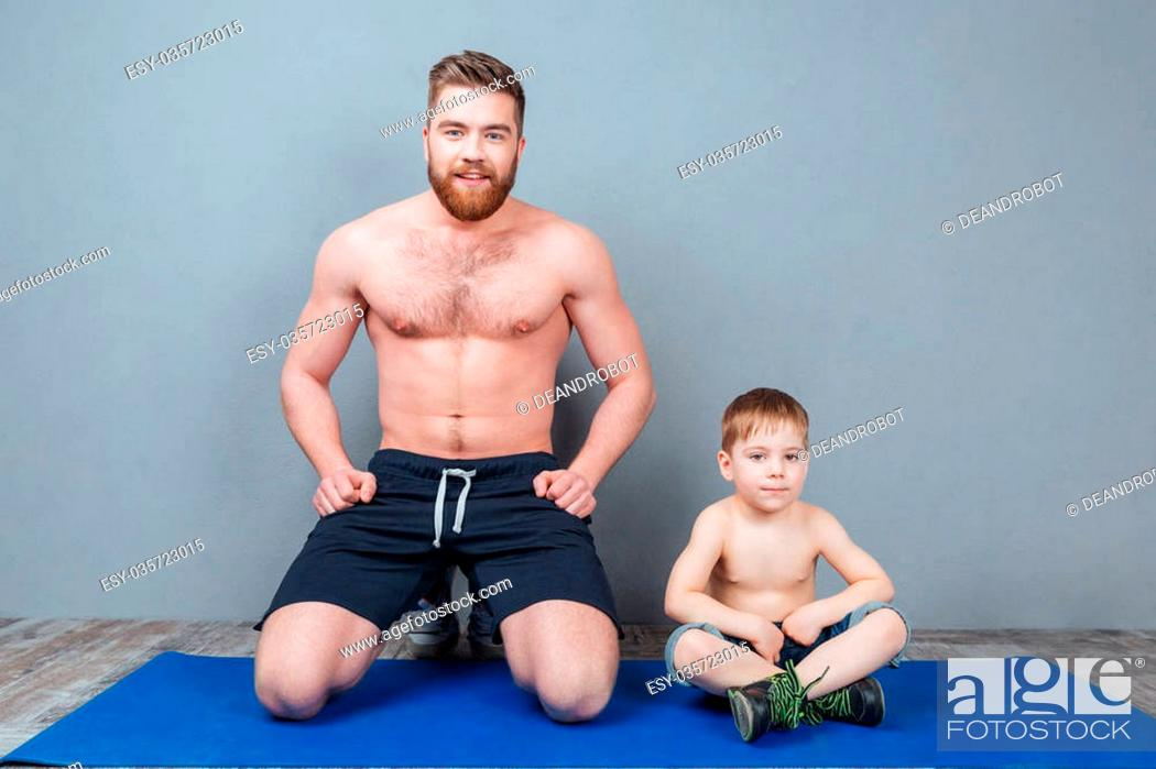 Stock Photo: Happy dad and song sitting on blue yoga mat together.