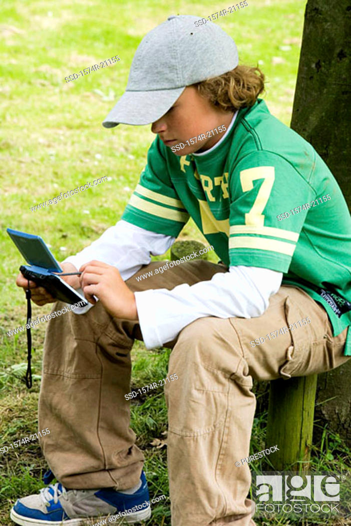 Stock Photo: Side profile of a boy using a personal data assistant in a park.