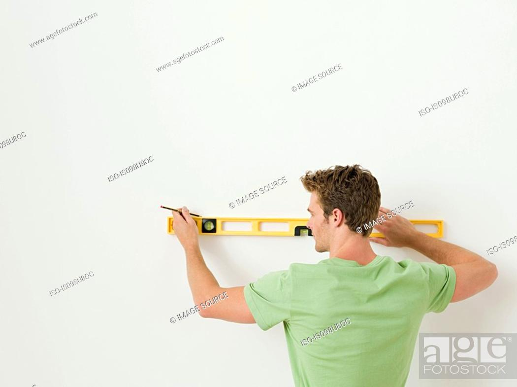 Stock Photo: Young man using spirit level on wall.
