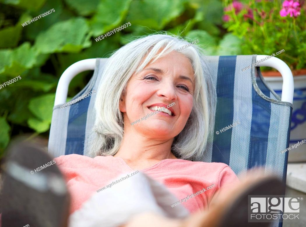 Stock Photo: Germany, Bavaria, Mature woman sitting in lawn chair.