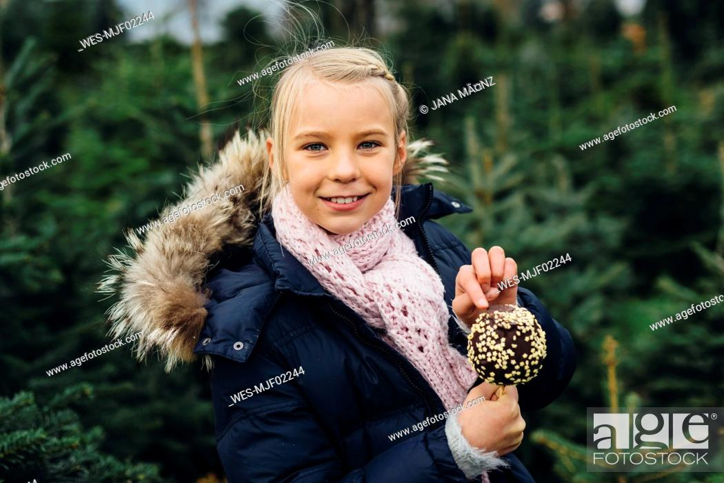 Stock Photo: Little girl standing in front of fir trees holding chocolate dipped apple.