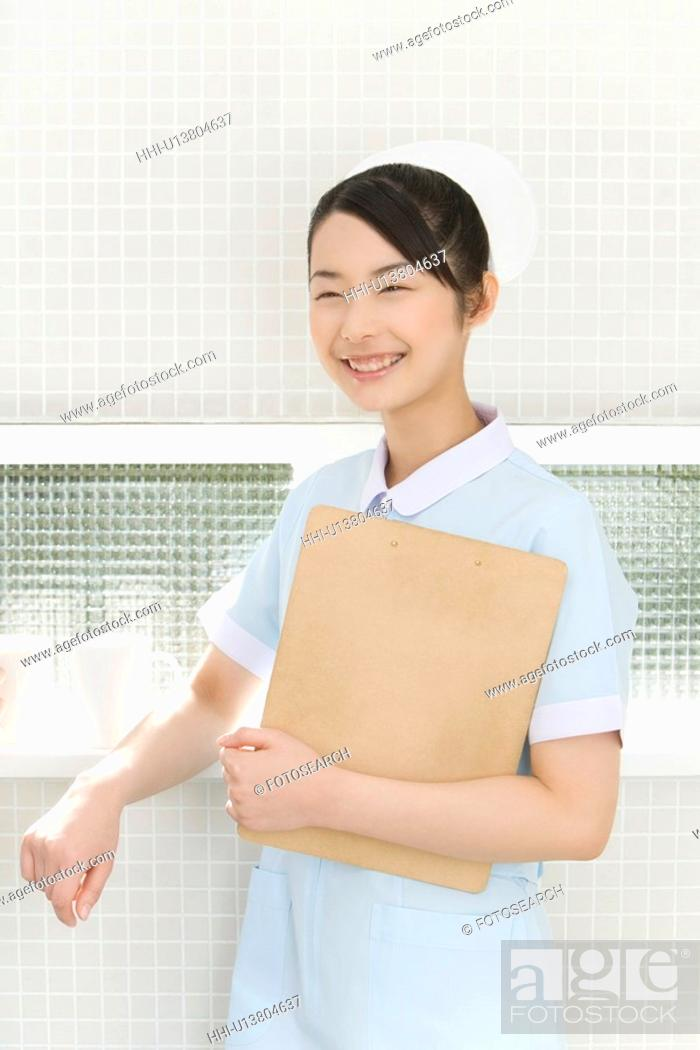 Stock Photo: Portrait of a nurse holding a clipboard, smiling, front view.