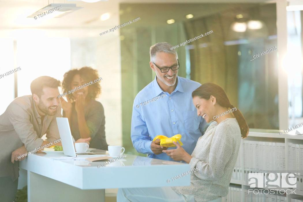 Stock Photo: Businessman giving gift to businesswoman in office.
