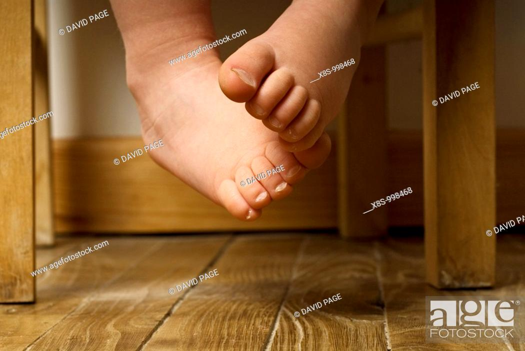 Stock Photo: Stock photo of a toddlers bare feet dangling off a chair.