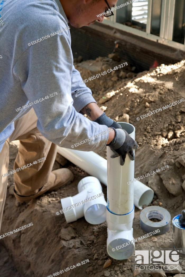 Stock Photo: Poly Vinyl Chloride, PVC, Pipes being installed for rainwater harvesting system at new home construction, California.