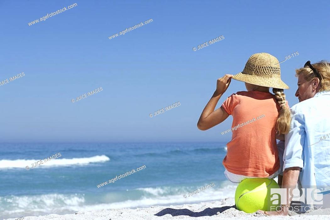 Stock Photo: Grandmother and granddaughter 7-9 sitting on beach, looking at horizon over sea, rear view.