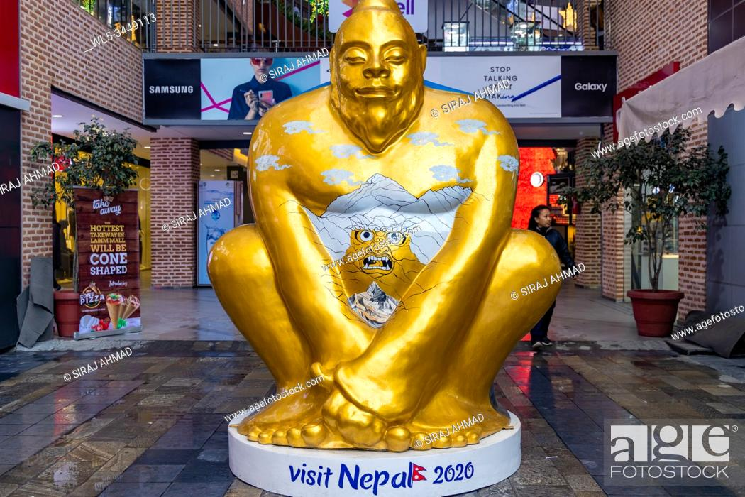 Stock Photo: Giant golden mascot of a Yeti, a mythical creature, sits at the entrance of a mall. Yeti mascot is chosen for the promotion of Visit Nepal 2020.