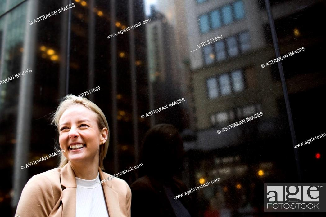 Stock Photo: Close-up of smiling businesswoman standing by glass window with reflection.