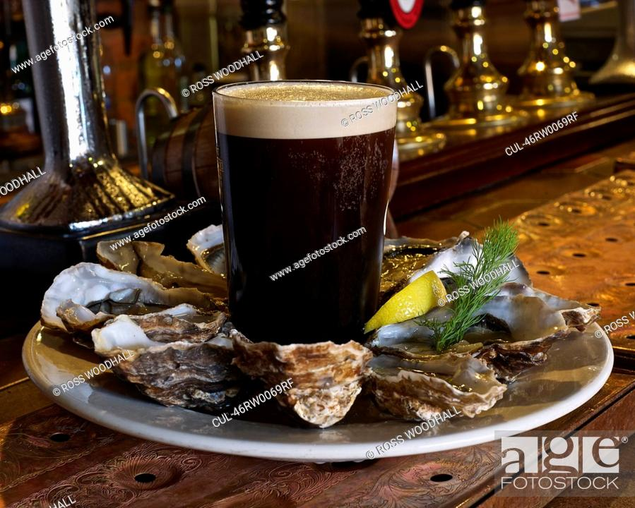 Stock Photo: Plate of oysters and stout in bar.