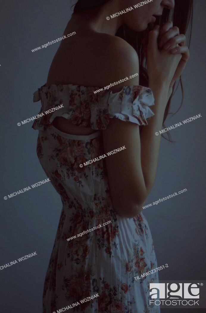 Stock Photo: Young woman wearing floral summer dress standing alone.