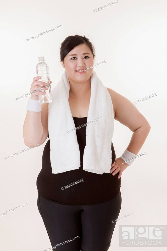 Imagen: Young woman holding a bottle of water and smiling at the camera.
