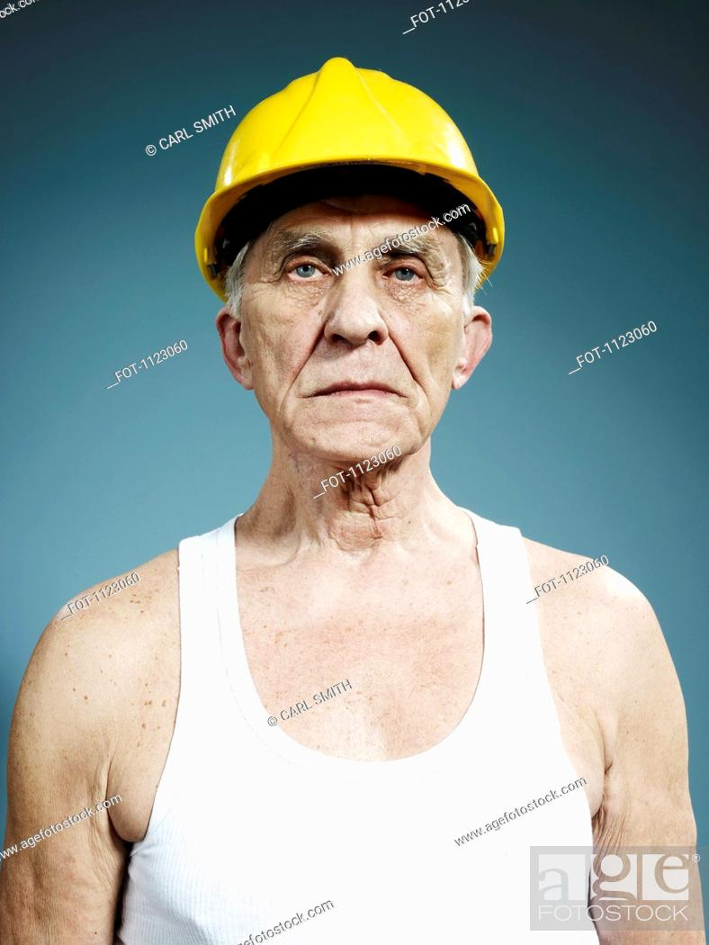 Stock Photo: A serious senior man wearing a hardhat and tank top.