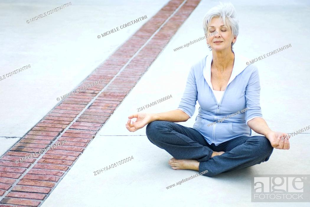 Stock Photo: Senior woman sitting in lotus position, eyes closed.
