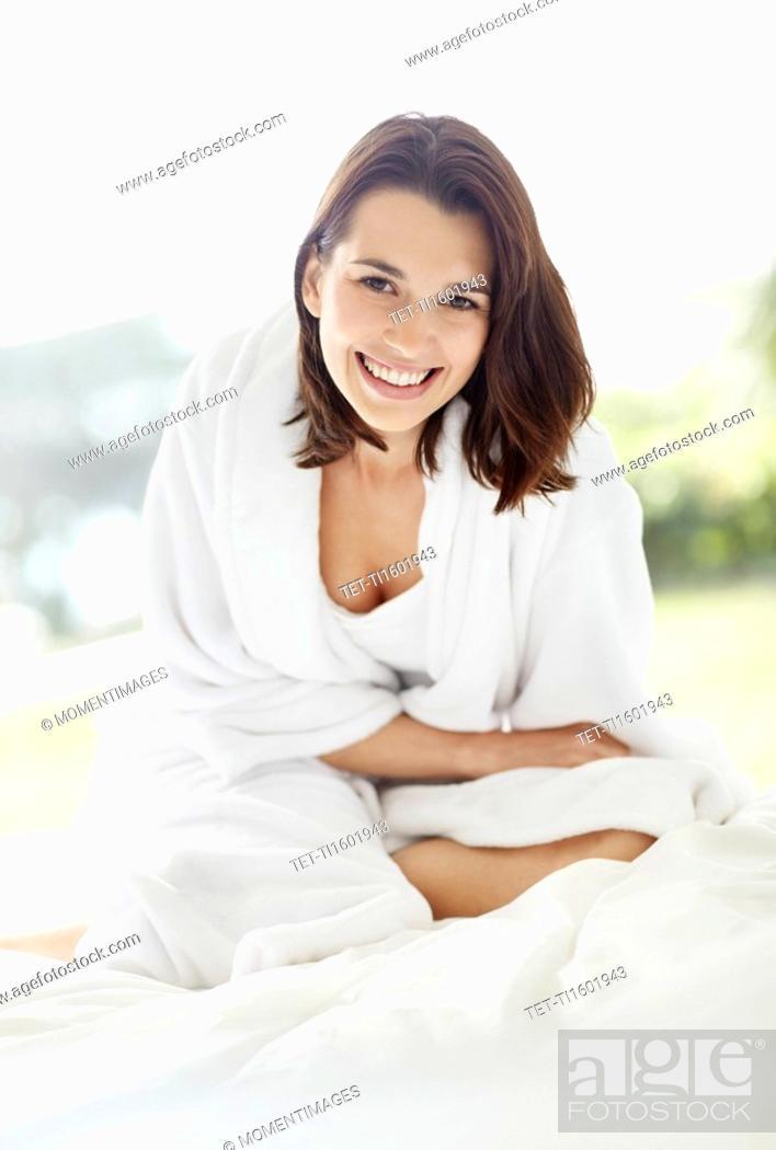 Stock Photo: Smiling brunette woman wearing a bathrobe.