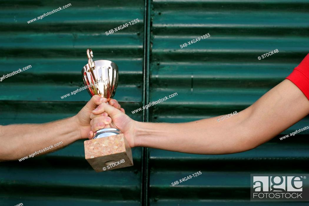 Stock Photo: Two men holding a goblet in hands in front of a wall made of corrugated sheet iron part of.