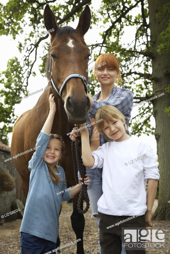 Stock Photo: Mother and children 5-6 7-9 with horse outdoors portrait.