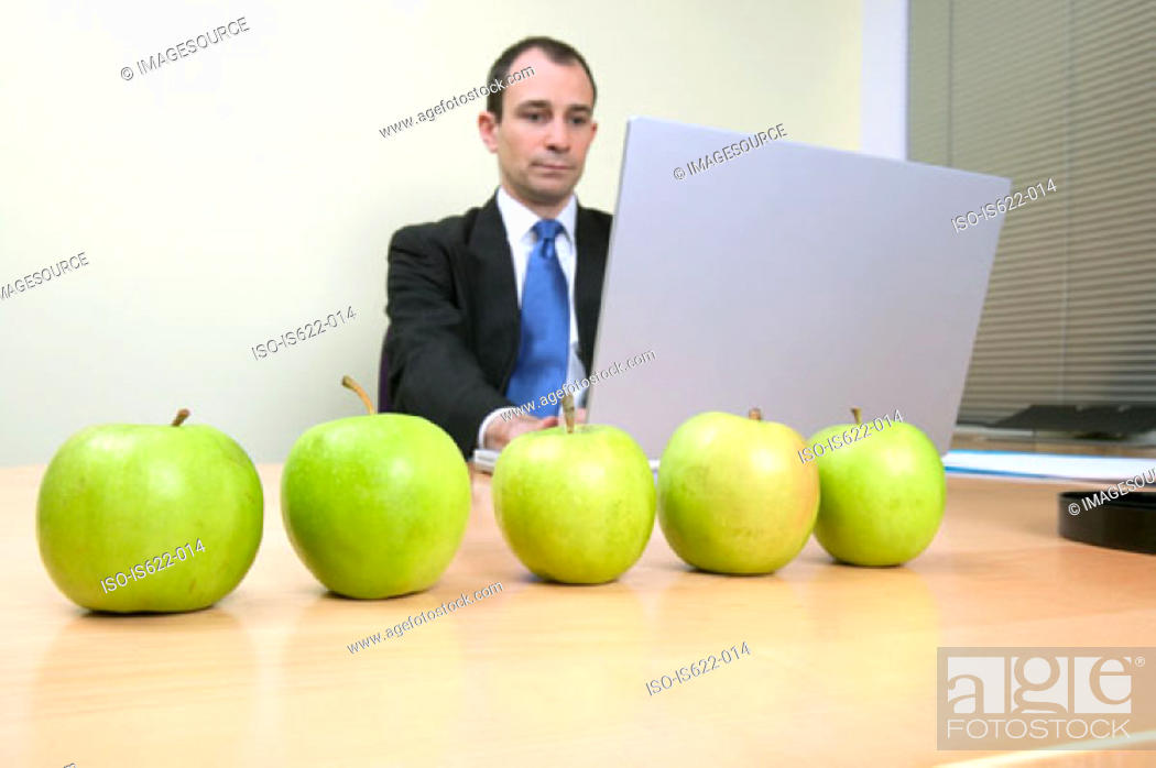 Stock Photo: Businessman with apples on desk.