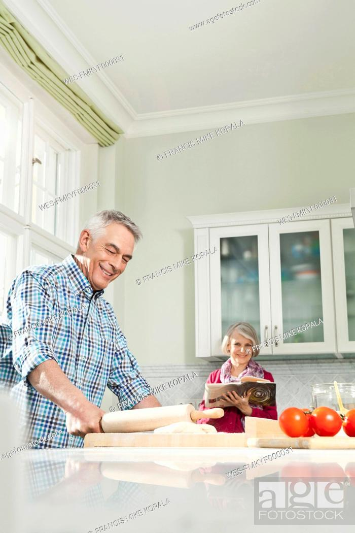 Stock Photo: Germany, Berlin, Man preparing food, woman with book in background.