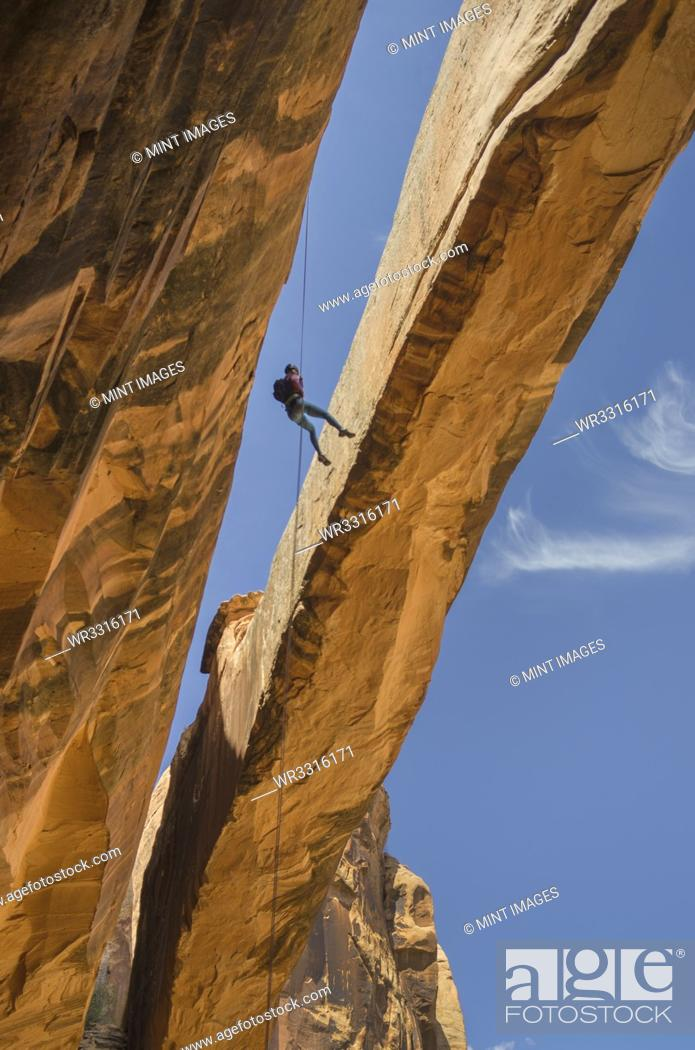 Stock Photo: Rock climber hanging on rope on arch.