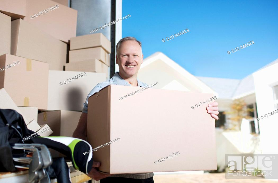 Stock Photo: Smiling man carrying box from moving van.