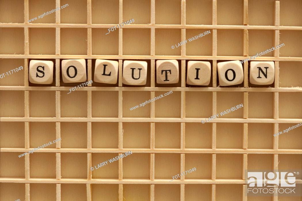 Stock Photo: A grid with lettered cubes spelling the word Solution.