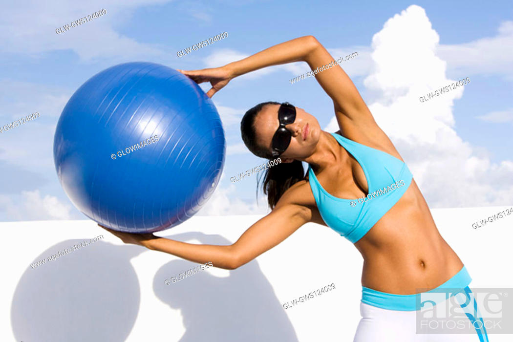 Stock Photo: Young woman exercising with a fitness ball.