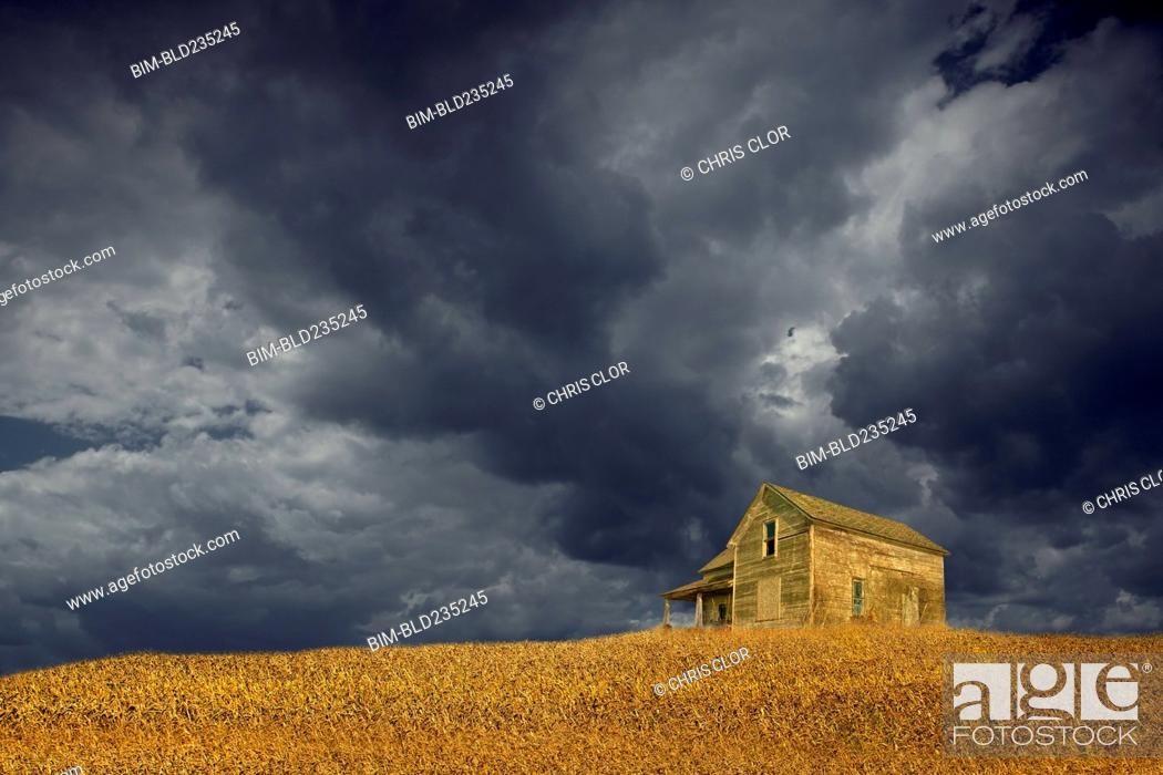 Stock Photo: Storm clouds over remote wooden farmhouse.