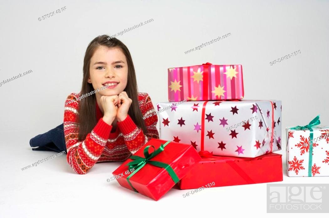 Stock Photo: Girl lying on front next to Christmas presents.