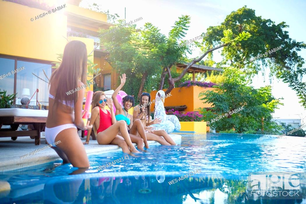 Stock Photo: Four young women having fun at the poolside.