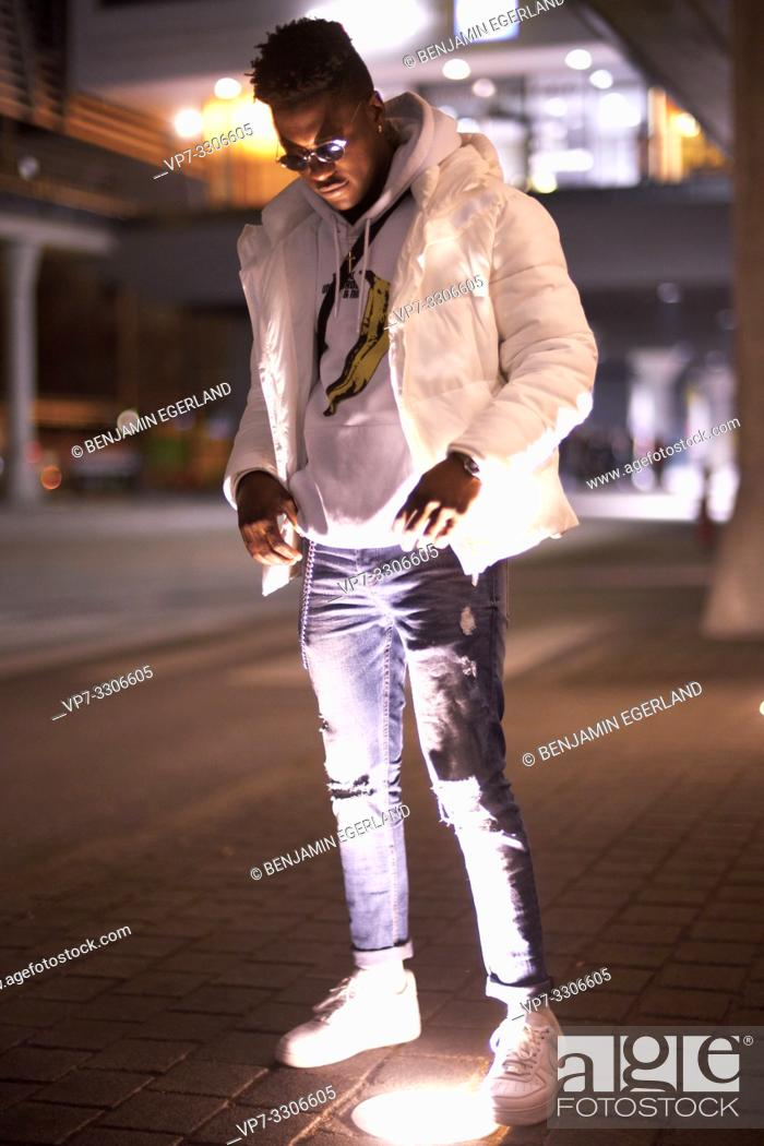 Stock Photo: young African man standing in light at street in city at night, in Munich, Germany.