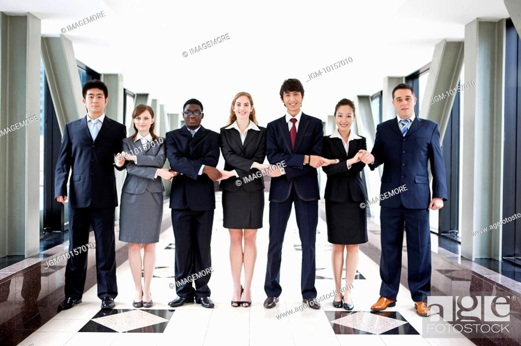 Stock Photo: Business people standing in a row and holding hands together.