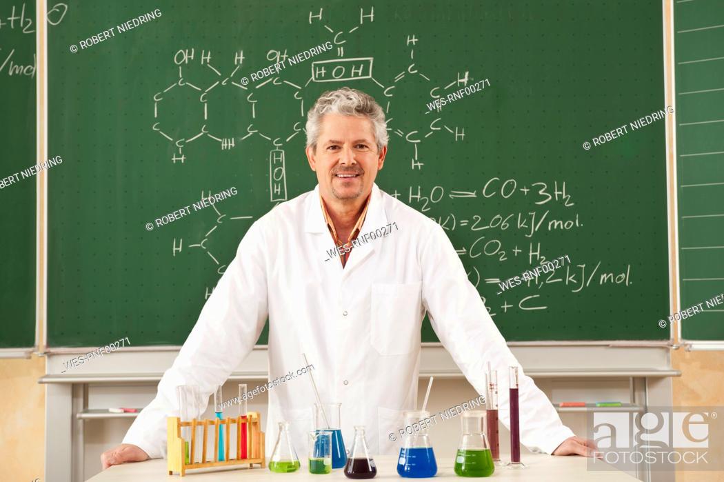 Stock Photo: Germany, Emmering, Senior man standing in chemistry lab, smiling, portrait.