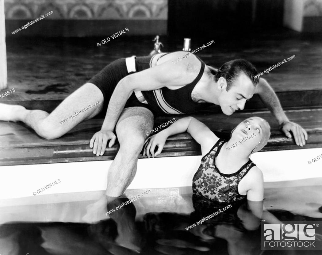 Stock Photo: Man bending over to kiss a woman in a swimming pool All persons depicted are not longer living and no estate exists Supplier warranties that there will be no.