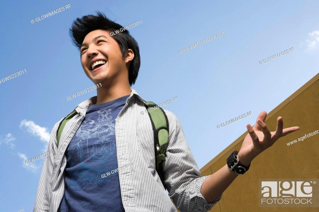 Stock Photo: Low angle view of a young man carrying a bag and laughing.