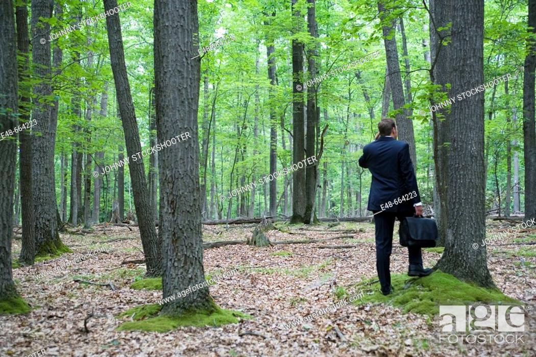 Stock Photo: Portrait of young businessman in forest with cellular phone.