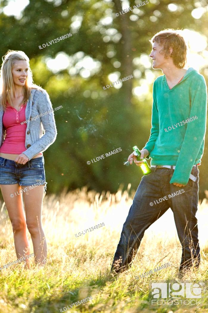 Stock Photo: A young couple standing in a field, man drinking and smoking.