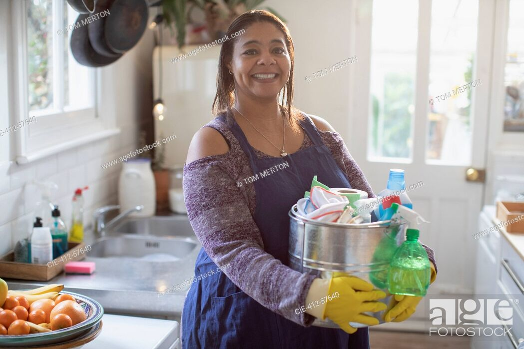 Stock Photo: Portrait smiling woman with cleaning supplies in kitchen.