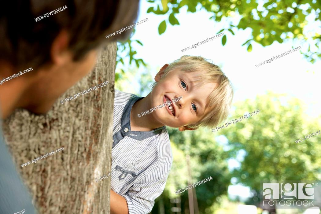 Stock Photo: Germany, Cologne, Father and son playing head and seek, smiling.