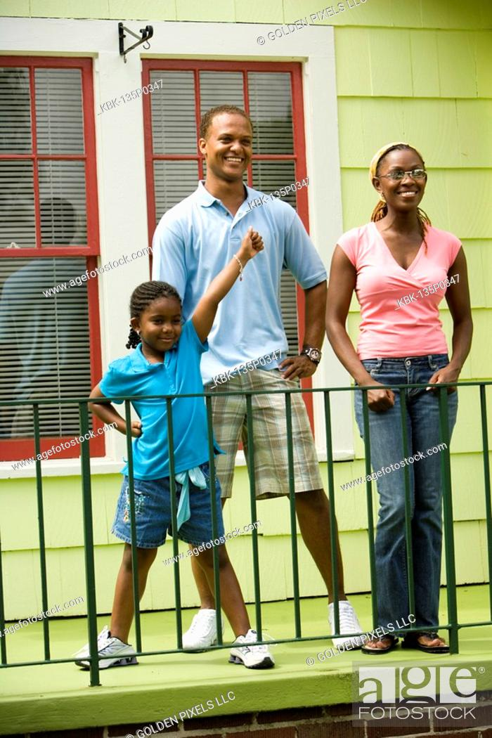Imagen: Cheerful family standing by a railing outside a house.