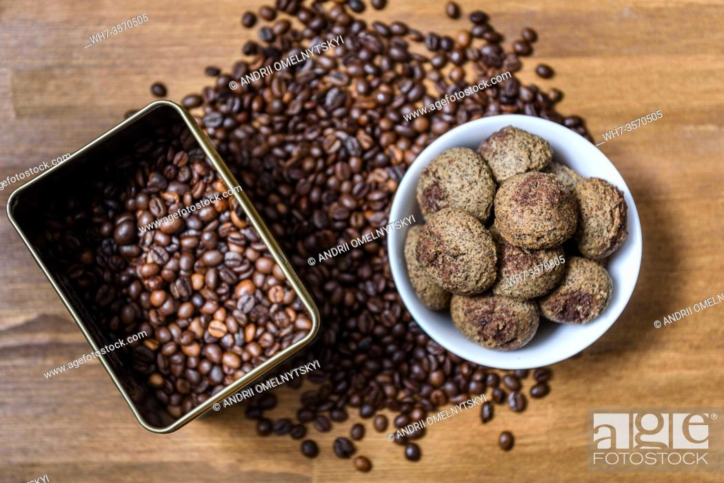 Imagen: coffee cookies in a white plate with coffee beans on wooden brown table.